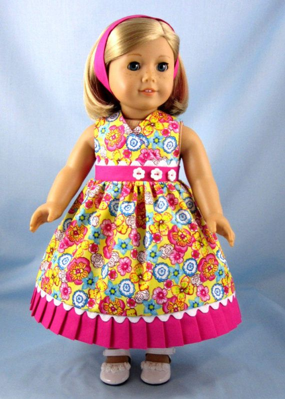 Your 18 Inch American Girl doll will be ready for summer fun or a tropical vacation when she dons this colorful sundress and headband combination! The dress features a sunny cotton print with an assortment of flowers in shades of yellow, pink and blue scattered over a bright yellow background. The dress has a wrapped bodice and gathered skirt. The waistband and hand-pleated hem band features a bright pink quilters cotton (photo 3.) Extra detail is provided by wide white rick rack inserted…