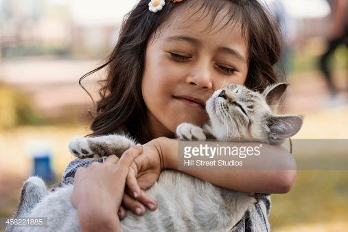 Stock Photo : Hispanic girl cradling cat