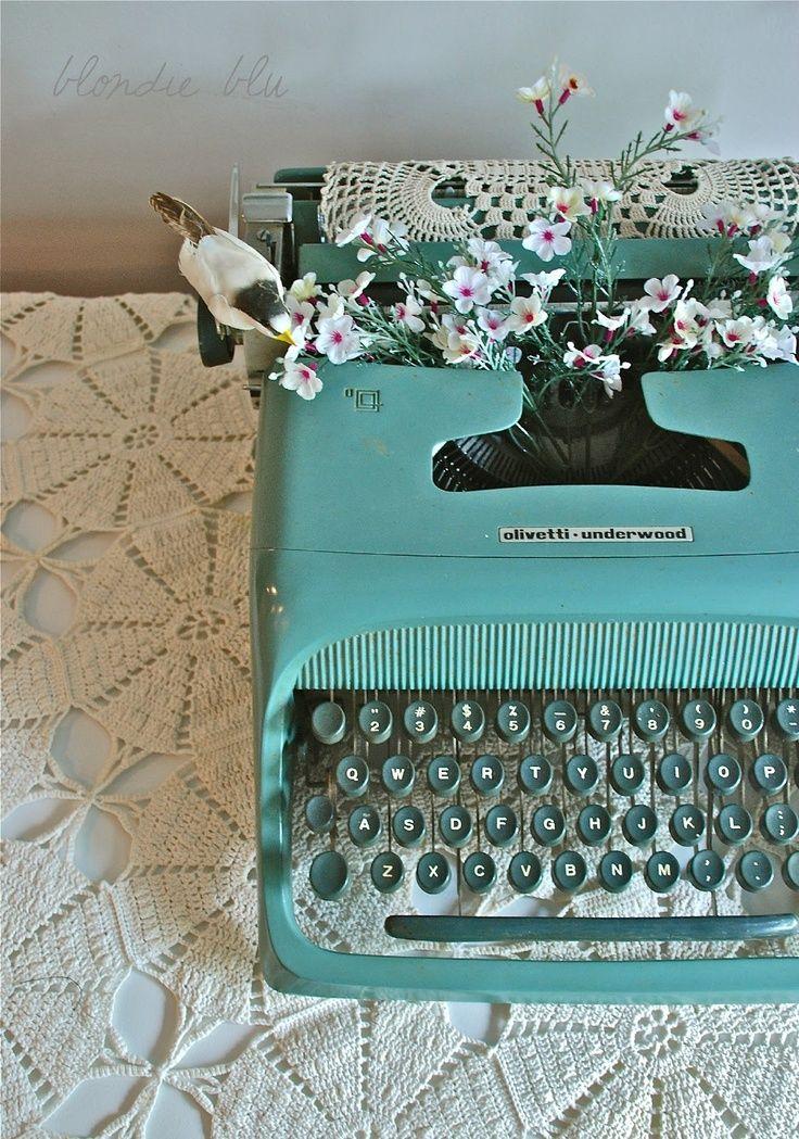 Turkos skrivmaskin (Den här tillhör en författare som ligger på latsidan. Det är lite svårt att skriva med blommorna i vägen).