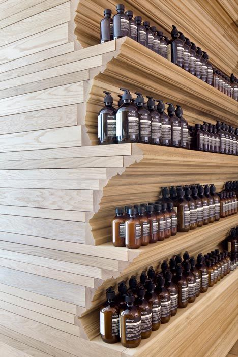 Cornices are commonly used to decorate the junctions between walls and ceilings, but at the new Boston shop for skin and haircare brand Aesop, cornices cover the walls and form shelves for the brand's signature brown bottles.
