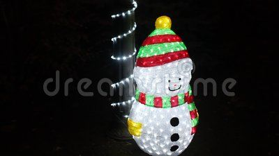 Snowman Christmas lights on the ground besides a pole adorned.