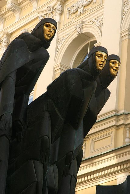 Black-robed, gold-faced muses symbolizing Drama, Tragedy and Comedy on the facade of the National Drama Theatre in Vilnius, Lithuania