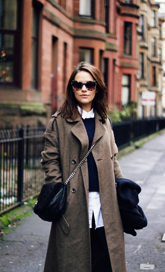 Tortoise shell sunglasses, brown wool coat, black knit layered over an untucked white oxford, black skinny denim, and black cross body bag
