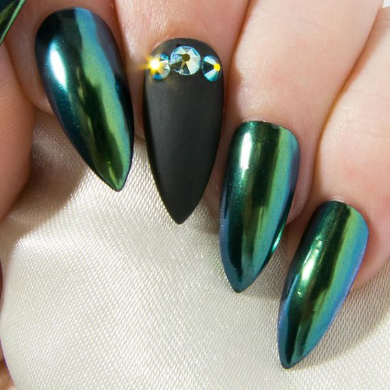 Green has never looked so good in this elegant chrome nail set. With a jaw-dropping mirror finish that will shift through hues of golden-green, teal and blue, and a matte black accent nail adorned with glittering Swarovski® crystals, the wicked witch hers