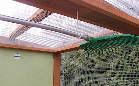 Chicken Coop Rake Hung Up And Out Of Way.  there are a lot of good suggestions on this blog.  sand under roosts and deep litter on top of soil composts in place.  nice coop too.