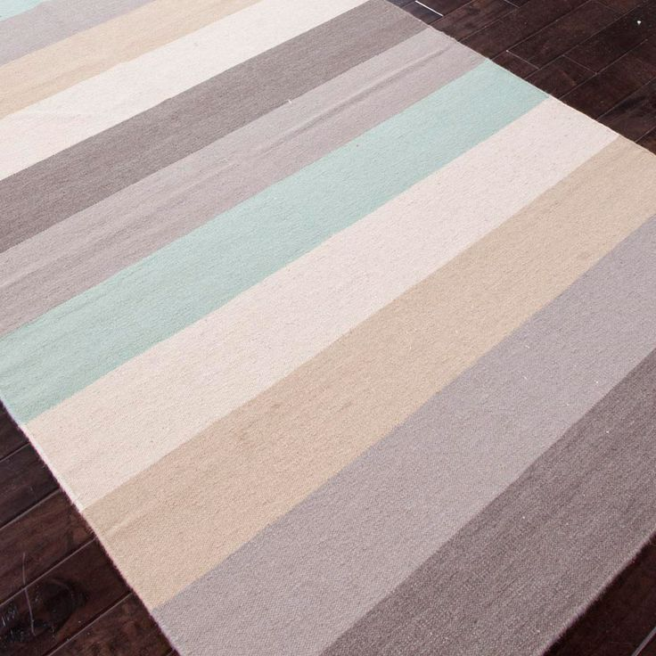 Soft stripes in a sea-inspired palette decorate the modern Anais rug. Part of Jaipur's Maroc collection, this rectangular floor covering invites with classic style. Notes of green, gray and beige; 100% wool; Flat weave; Reversible; Rug pad recommended; Vacuum regularly and spot clean with mild soap and cold water