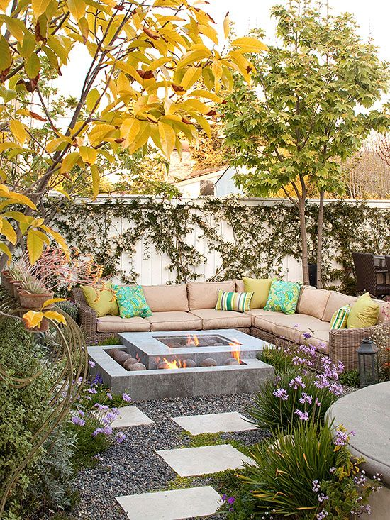 A long sectional couch frames a modern double fire pit in this backyard. Dark rock decorates the area and stone tiles add in some visual interest. The arrangement creates an outdoor living room where a family can lounge on hot summer days as well as gather on cool fall evenings.