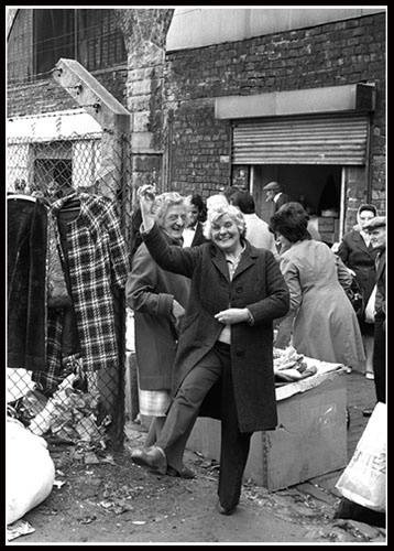 """""""The quick wit and humour of the Glasgow people is shown in this photograph. I mentioned how people react differently when they spot the camera pointing at them. As you can see, this woman decided to ham it up and demonstrate the Highland Fling. One quick hooch! and the moment was captured.""""- D.W. Robertson"""