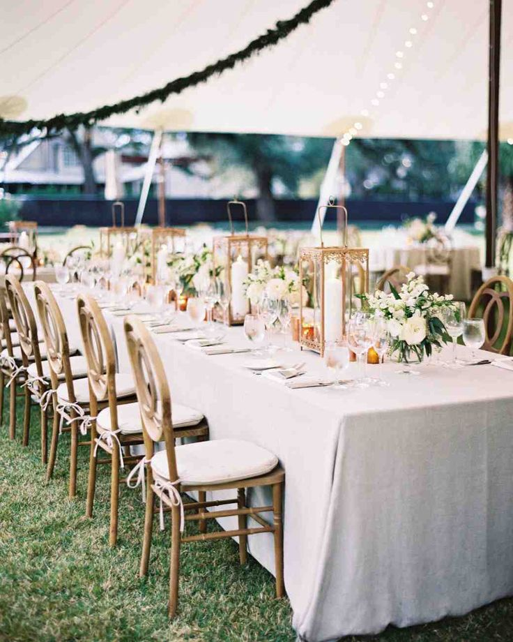 A Rainy, Rustic-Chic Wedding in South Carolina | Martha Stewart Weddings - Garlands of eucalyptus and strings of lights hung over a mixture of farm and round tables. Centerpieces were copper lanterns, copper candle vessels, and floral arrangements of white flowers and greenery.