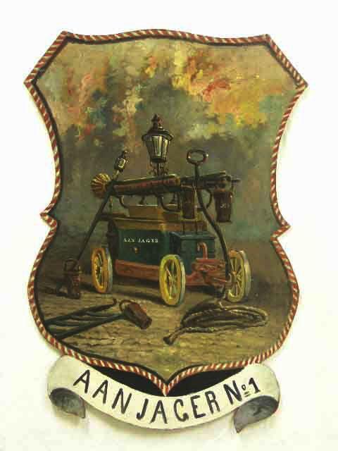 vaandels van de brandweer; 1. beschilderd karton; afbeelding van brandspuit met lantaarn - op stok - met attributen als emmertjes en touw; opschrift: AANJAGER No 1; rood-witte koordbeschildering als rand; achterop: kroon