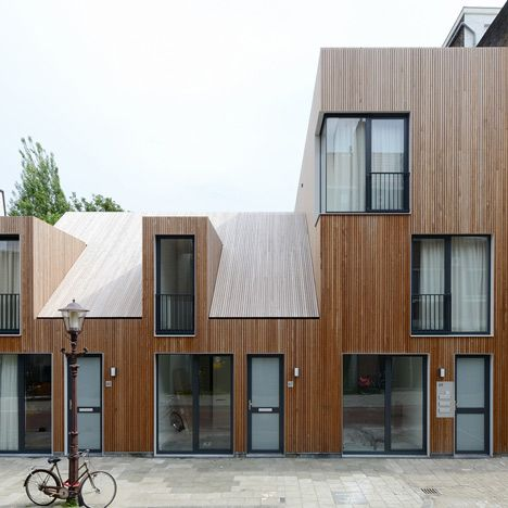 This small housing development in Amsterdam by Dutch studio M3H Architecten features five homes, with untreated timber cladding and angular dormer windows.