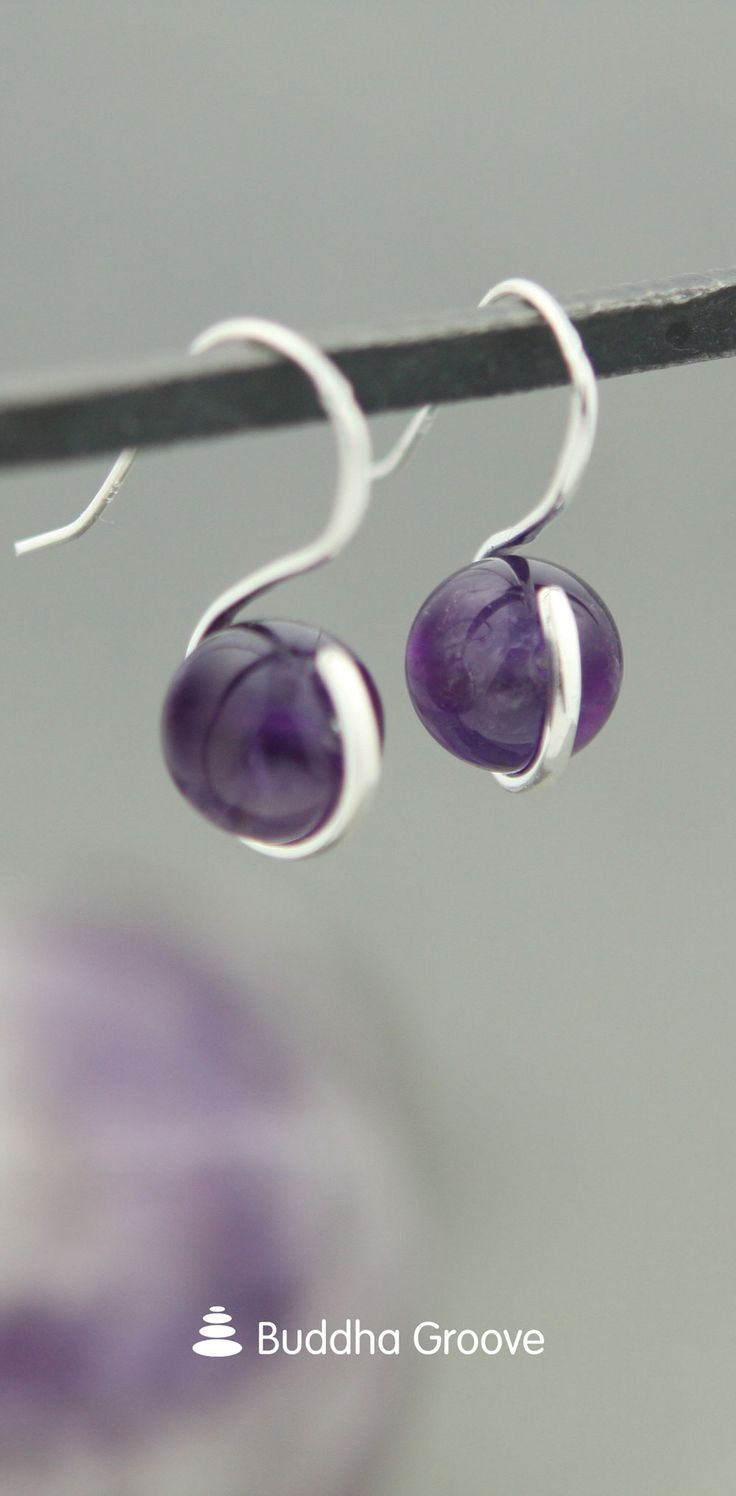 Amethyst is said to contain special metaphysical qualities, allowing those who use amethyst to tap into their inner divinity and access higher plans of consciousness. Featuring a unique S-curve design, these earrings are made with spinning amethyst orb beads that can help you access those hidden depths within yourself.
