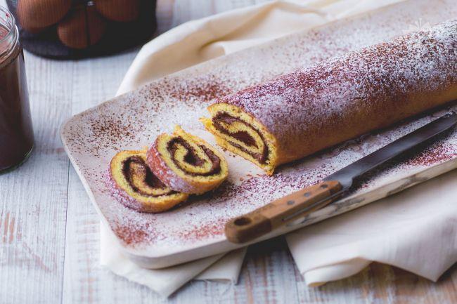 Il rotolo alla Nutella è un dolce preparato con una base di pasta biscotto arrotolata e farcita con una deliziosa crema al cacao e nocciole.