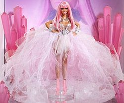 Nicki Minaj - A plastic doll on display wearing a gauzy, pale gown with a neon pink wig and matching stilettos.