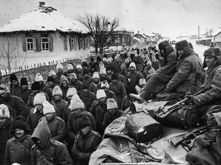 Stalingrad, Dec 1942: Romanian POWs trudge past Red Army troop carrier. Many Romanians wear funny fur caps widely used by the Romanian army of the time. Very few Romanians returned from Soviet captivity.