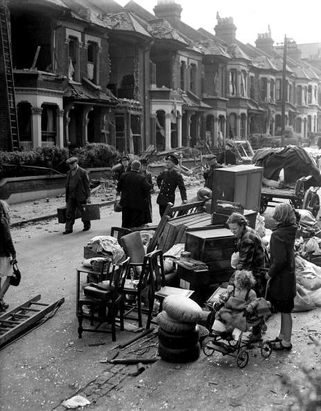 14th, September, 1940: People in the street with their furniture and belongings in a street in the London area, with their damaged homes in the background (Photo by Popperfoto/Getty Images)
