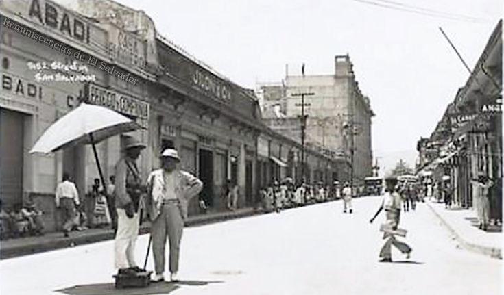 Un policía de tránsito conversa con un caballero, un niño cruzando la actual Calle Ruben Dario, derecha Mercado Central o de la compañía, consumido por un incendio en 1961 al, fondo se observa el histórico edificio conocido como El Telégrafo, construido en 1936. durante el gobierno del General Maximiliano Hernández Martínez.