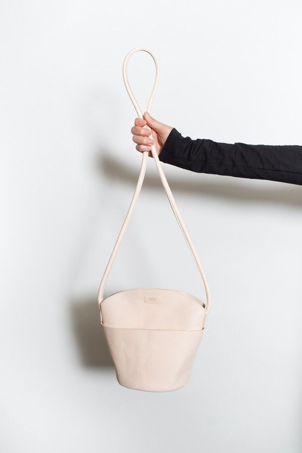 The Arc shoulder bag from ARE Studio - a minimal bag featuring thoughtful details. Magnet closure, circular base, rolled strap and an exterior pocket, perfec...