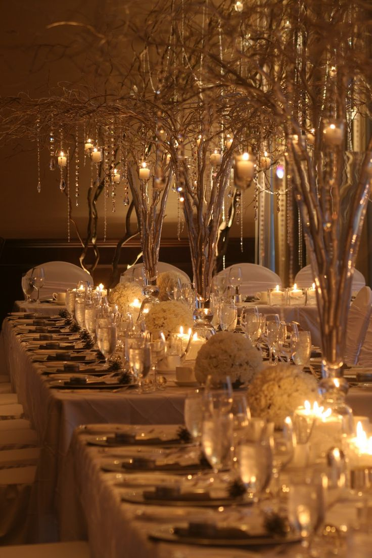 I like the branches with the crystal beads and candles hanging the lighting only. The table cloth needs to be black and table settings more simple. These settings are too fancy for me.