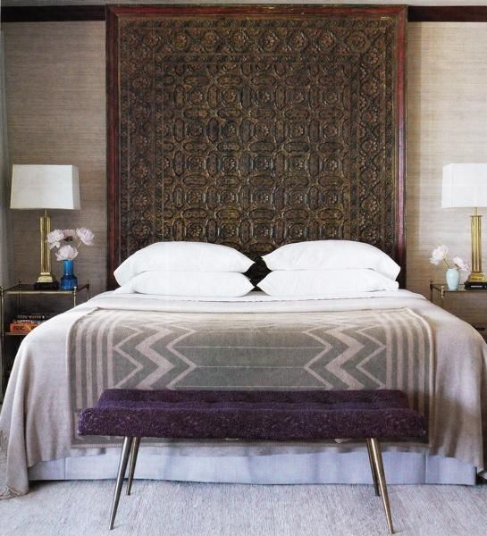 purple & gray Moroccan bedroom design with carved wood panel used as headboard, crisp white bedding, geometric cashmere gray throw blanket, violet purple tufted modern bench with stainless steel legs, gray wool rug, brass two tiered glass tables nightstands, silver lamps and gray grass cloth grasscloth wallpaper. brown gray purple bedroom colors.