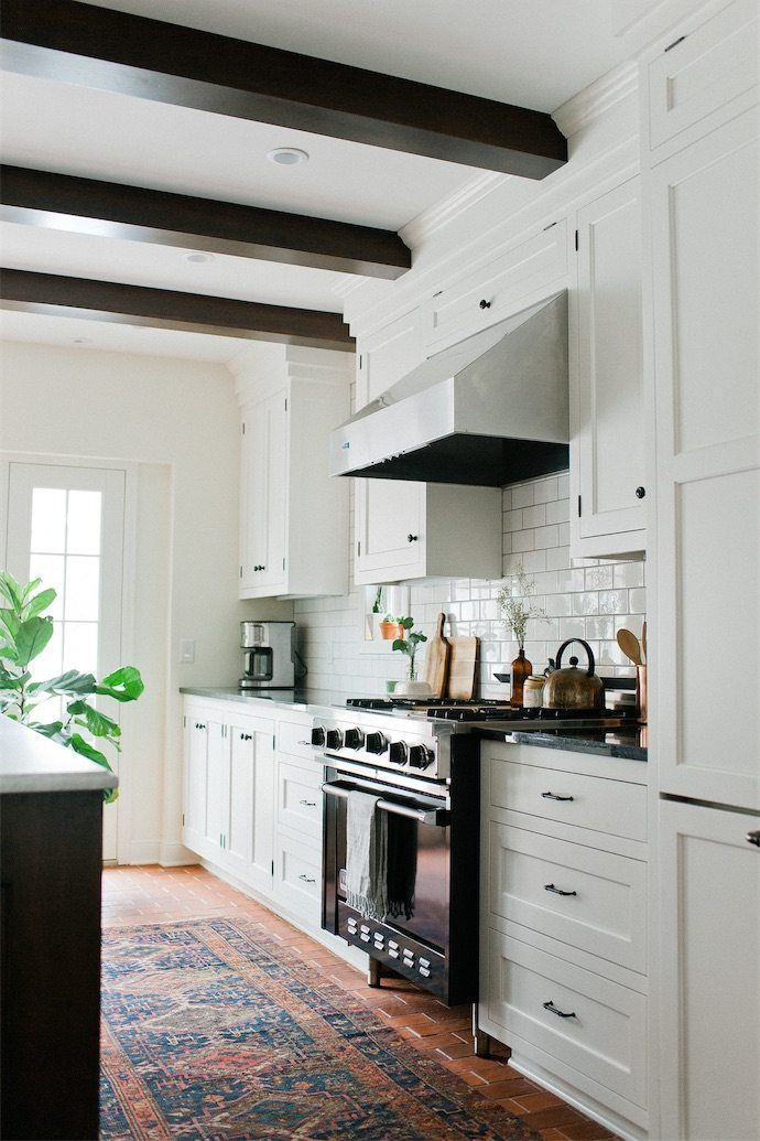 bright and beautiful modern kitchen with in all white with patterned carpet