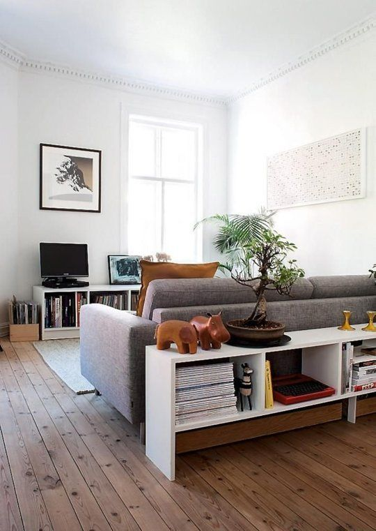 Place a console table behind a free floating couch for extra storage