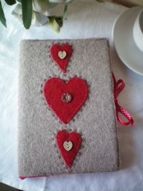 Handmade Notebook Cover in Fawn with Three Red Hearts by Linda Chapman. This A6 sized felt notebook cover comes complete with a notebook; the pages of which are white and are blank for your notes and/or sketches. A decorative ribbon ties the book together when not in use. Cleverly, when the notebook is full, simply remove and buy another to slip inside the cover. £24.95