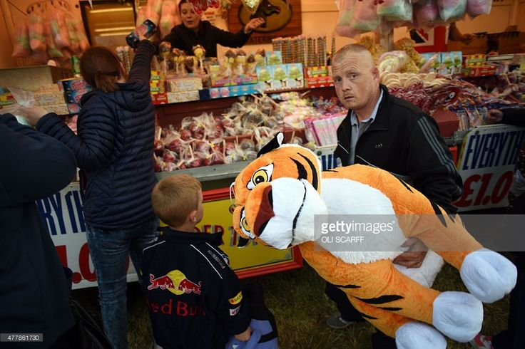 A man carries a large, soft-toy tiger which was won as a prize at The Hoppings fun fair, believed to be one of the largest travelling funfairs in Europe, on its opening day in Newcastle upon Tyne, North East England on June 19, 2015. The fun fair, which originally began as a Temperance Fair in 1882, comprises of over 300 attractions set up on the city's Town Moor. The fair runs until June 27, 2015 and is expected to attract 300,000 people.