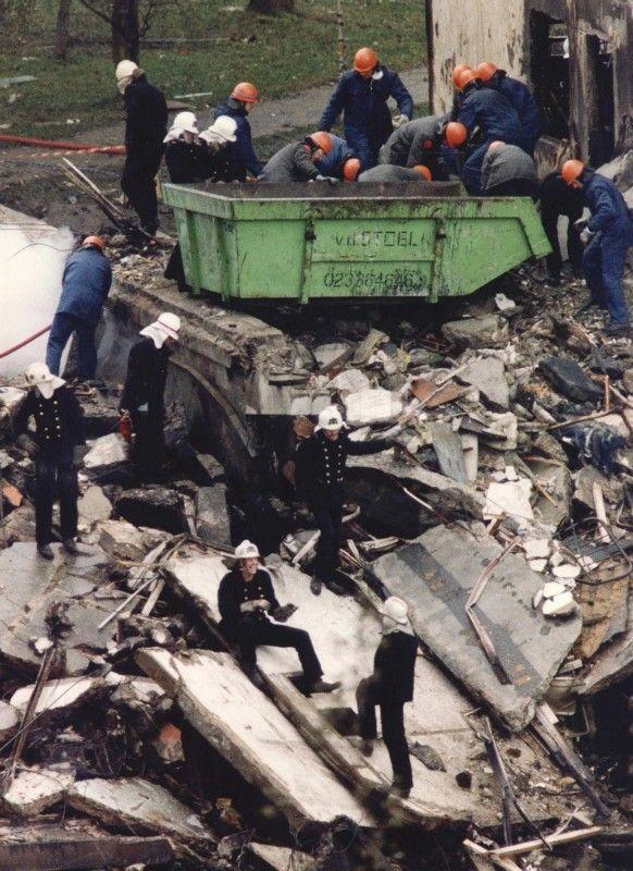 Reddingswerkers doorzoeken puinresten e.d. bij de grote container (achtergrond). ANP - Paul Vreeker