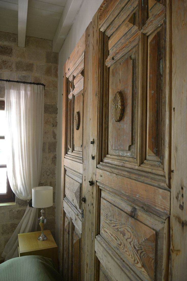 "EXCLUSIVE SUITES BOUTIQUE HOTEL. MEDIEVAL TOWN, RHODES, GREECE. - ""Katina"" suite. Bedroom. Behind the bed, Cypress wood door, ca 1920, Tripoli, Peloponese. - kokkiniporta.com"