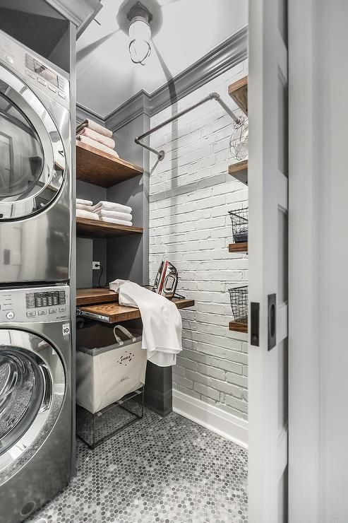 Beautifully Appointed Gray Industrial Laundry Room Is Equipped With A Stacked Gray Front Loading Washer And