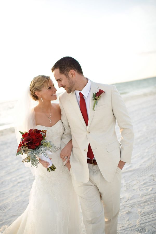 bride and groom walking on the beach, strapless lace Casablanca wedding dress, classic men's attire, red silk tie, red calla lily boutonniere, red rose and calla lily bouquet, romantic Christmas beach wedding