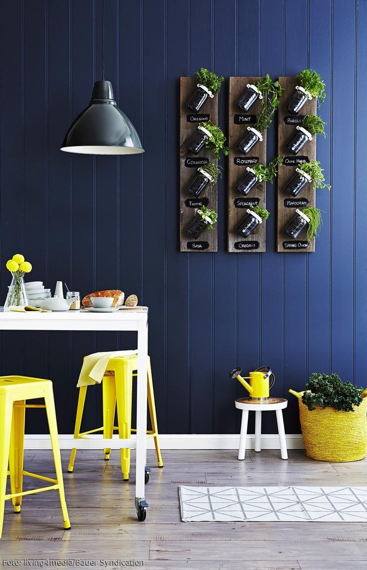 Die Mason Jar-DIY Gläser an der blauen Holzpaneelwand sind das tragende Stilelement in dieser Küche und sorgen für ein ruhiges Ambiente. Dank der blauen Wandfarbe setzen sich die gelben Hocker besonders gut ab. Der weiße Esstisch lässt sich dank seiner Rollen leicht verschieben und somit flexibel einsetzen. Für ein stimmiges Licht sorgt die dunkelblaue Deckenleuchte.