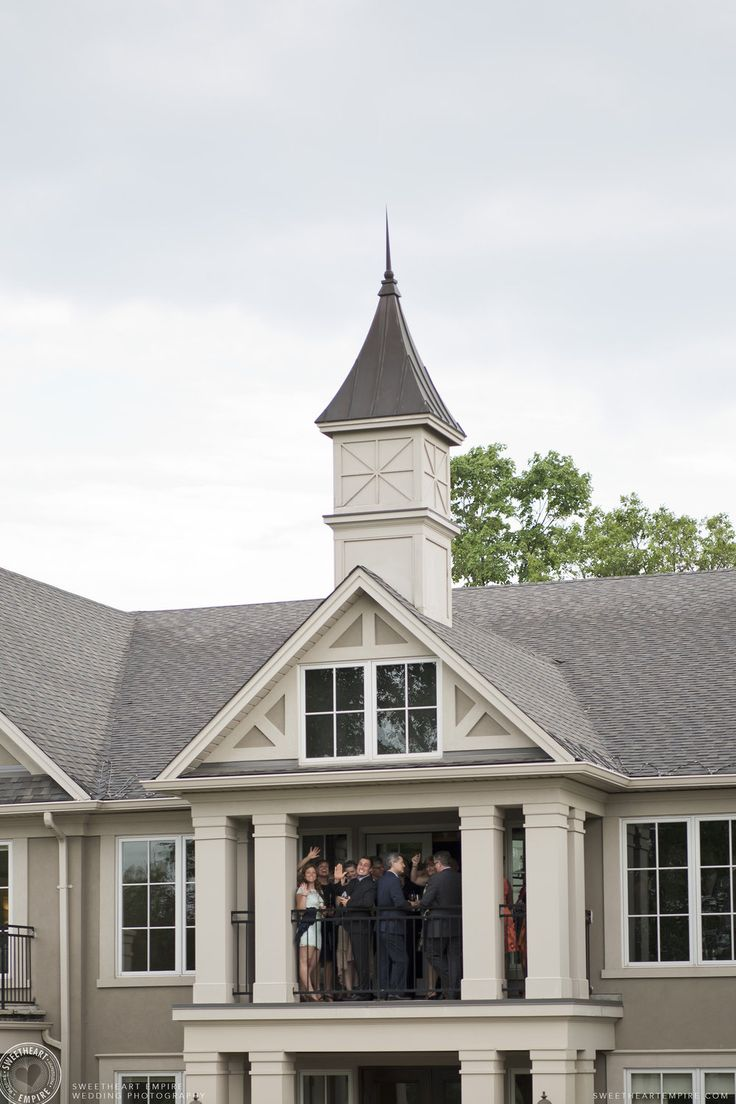 Wedding guests on the balcony at the Oakville Golf Club during cocktail hour. Oakville wedding photographer #sweetheartempirephotography