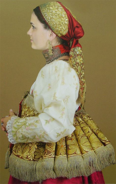 An intricately detailed, elegantly ruby and gold hued Russian traditional costume.