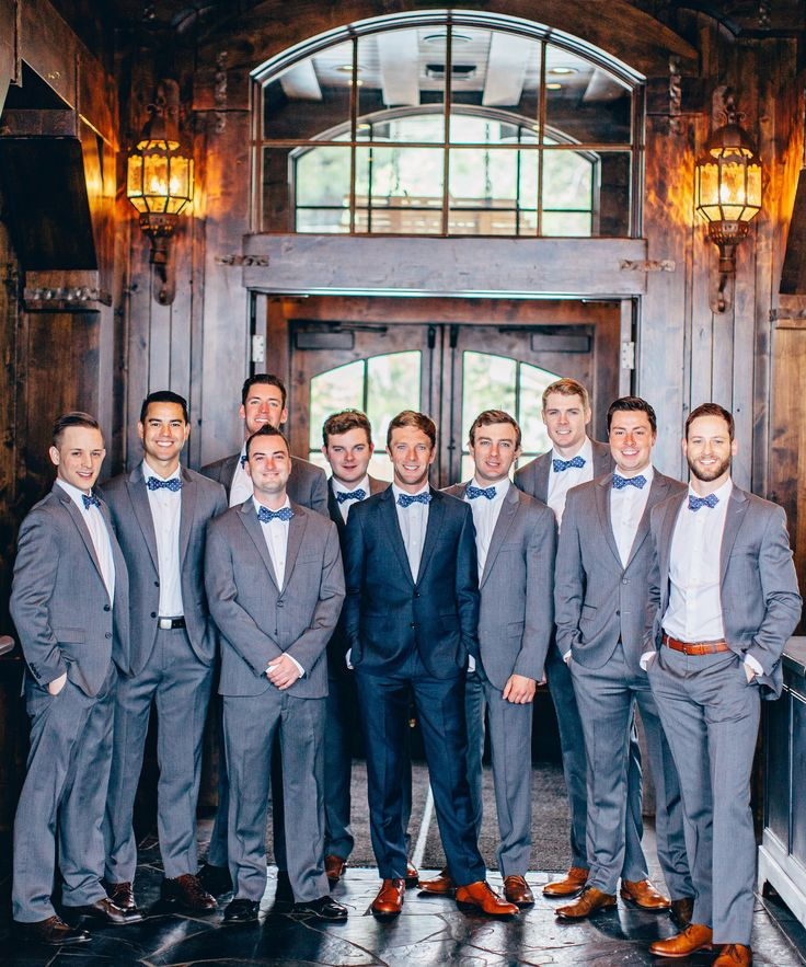 handsome grey tux groomsmen attire with blue bowties