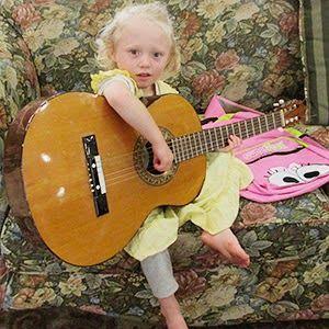 Josie Duggar strumming on the acoustic. It's bigger than she is, LOL! Soooo Cute! #Duggar #19KidsAndCounting
