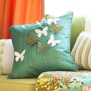 エメラルド色のシンプルなクッションカバーに、蝶の形にカッティングしたフェルトのモチーフが縫い付けられています。グラデーションカラーにすることで立体感が生まれていますね。
