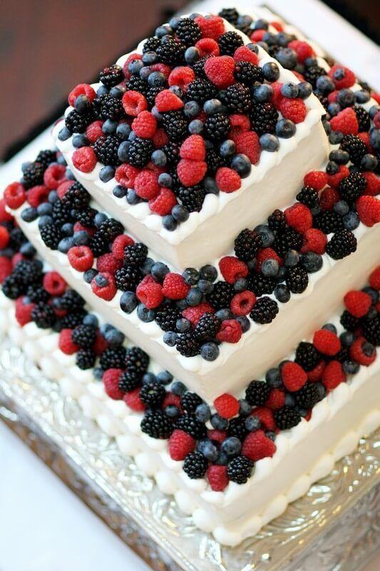 Ovocný patrový svatební dort s lesními plody. Zdobený malinami, ostružinami a borůvkami.   Patrový svatební dort