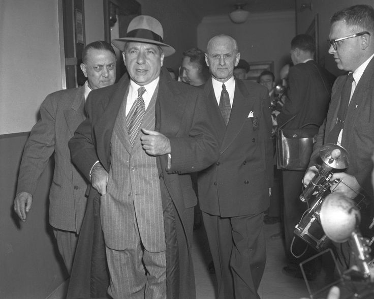 Frank Costello strides into the hearing room.