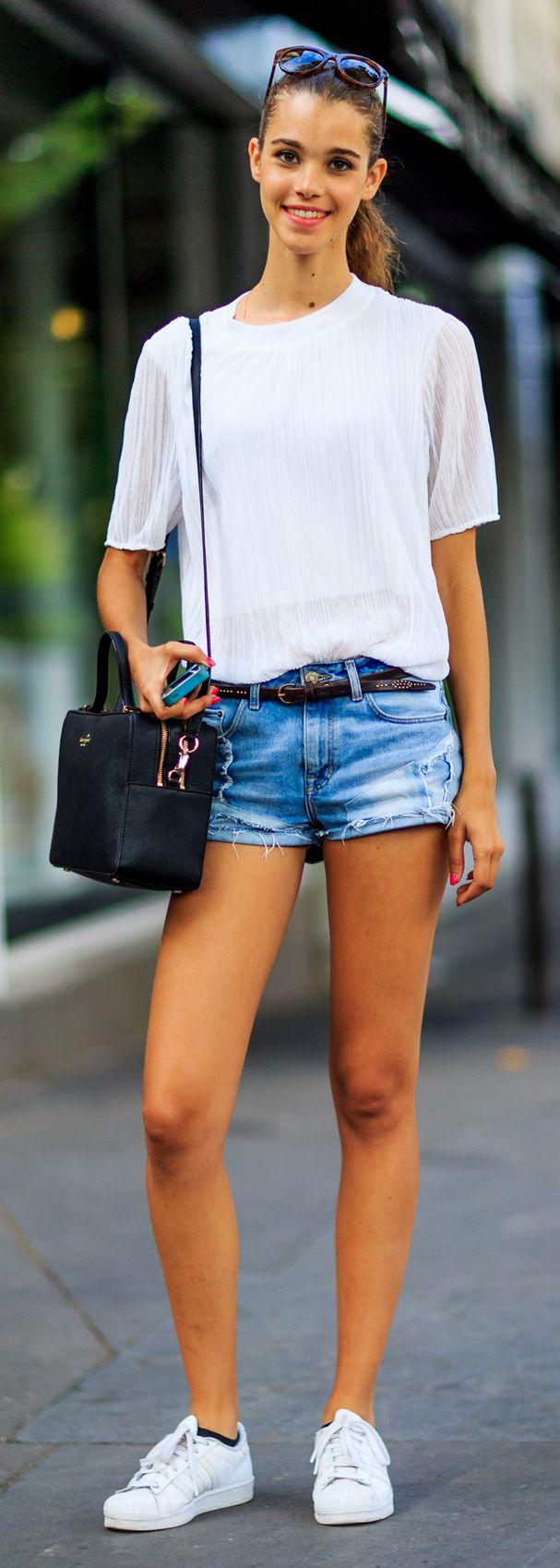 Un short en jean, un haut blanc, des baskets blanches et une pochette en cuir.