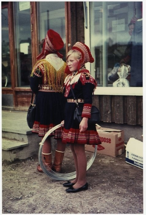 Two Sámi girls outside of a store; one holds a roll of baling wire; they both wear wool hats and dresses; one wears a scarf and boots, the other shoes; Kautokeino, Norway. Photographed by Katesa Schlosser, 1967 (via British Museum)