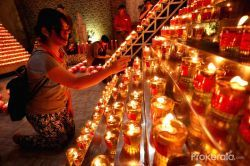 A woman lights candles to pray on the eve of the Chinese Lunar New Year at a temple in Palembang, South Sumatra, Indonesia