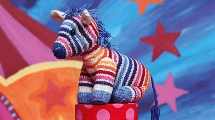 Ist sie nicht süß, die bunte Zebra-Dame Nora? In unserer Anleitung erfahren Sie Schritt für Schritt, wie Sie sich das Regenbogen-Zebra selber stricken können.