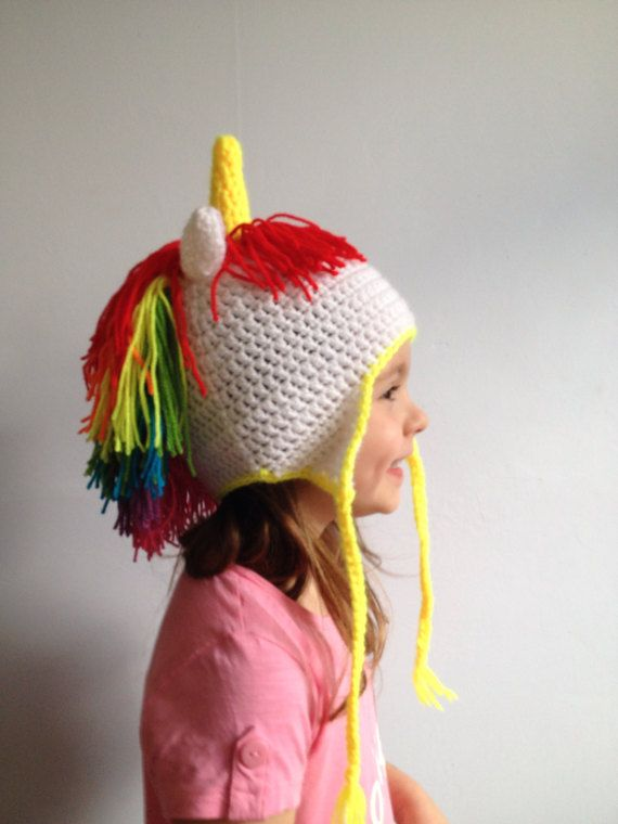 Rainbow Unicorn Hat.  For all the unicorn lovers out there.....this hat is a delight, just making it gives me a smile.  It features:  - a rainbow mane - horn - plait ties and trim in a colour of your choice (choose from red, orange, yellow, green, blue, purple, pink or white). Please choose your colour in the variation dropdown box border/plait colour.  Machine washable. 30 degrees.  Available in baby, child, teen/adult sizes.  This hat is made to order, please allow for 2-3 days be...