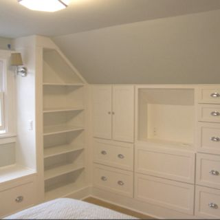 Built in storage. This is pretty much our attic bedroom! That's a lot of storage and nice touch is the niche for a TV. It may be possible to use IKEA chest drawers to acheive this. Or find a talented carpenter..