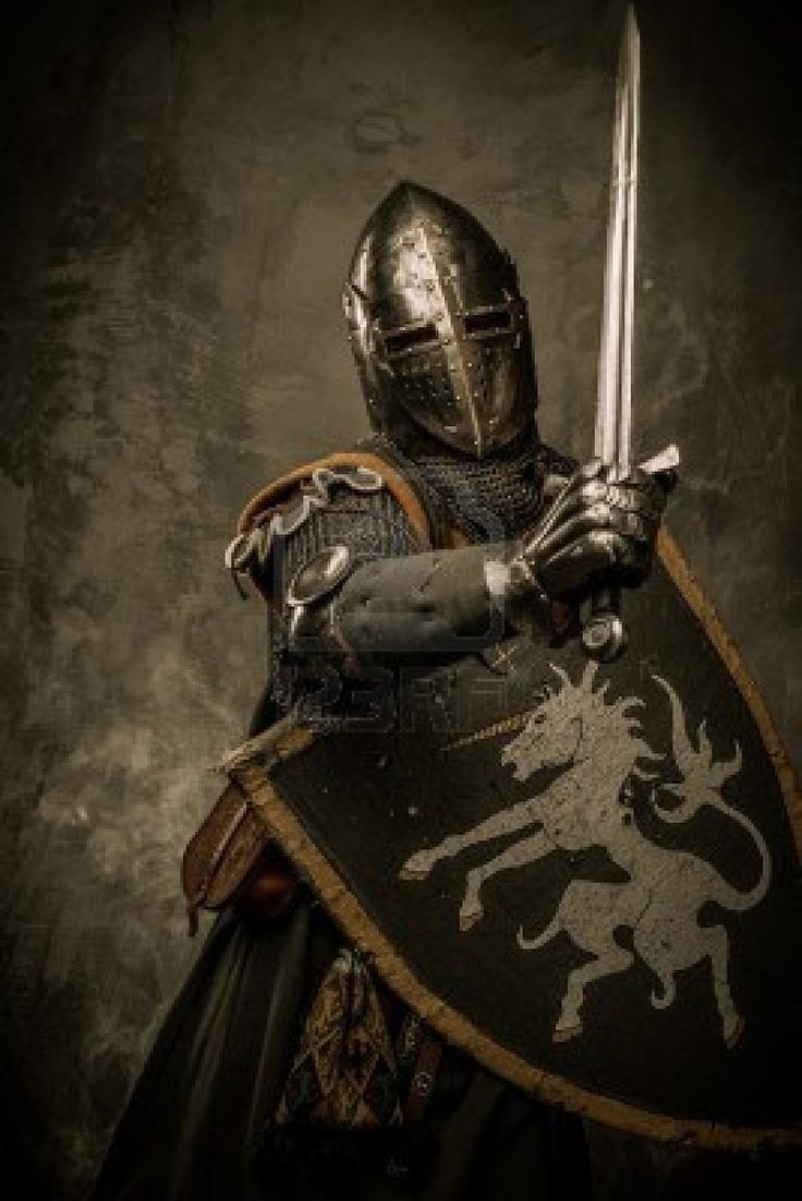 knight wearing sugarloaf helm and chain mail, armed with an arming sword and wooden shield