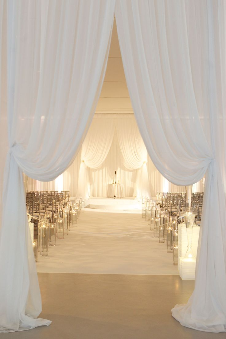"Guests entered a beautiful ballroom embellished with vanilla drapery for the Chicago ceremony. The white aisle was lined with ""floating"" candles in rectangular glass vessels in varying heights. #WeddingEntrance Photography: Bob & Dawn Davis Photography. Read More: http://www.insideweddings.com/weddings/modern-purple-blue-white-wedding-at-contemporary-chicago-venue/541/"