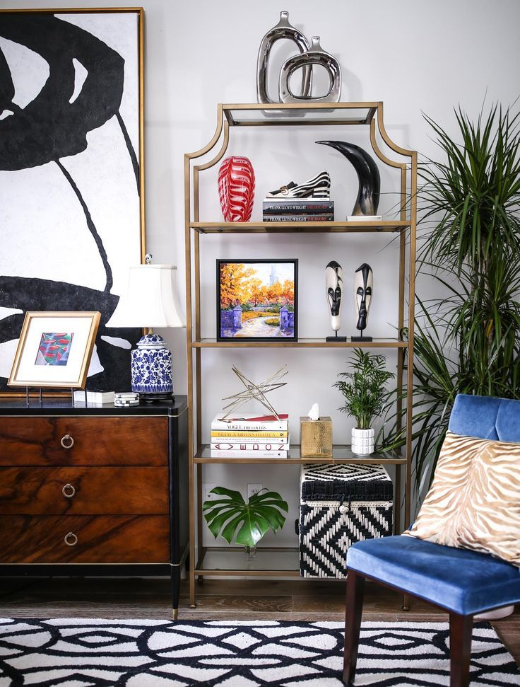 My home office! // Gold and glass etagere bookshelves, blue velvet accent chair, gold zebra pillow, black and white area rug, burlwood dresser with gold accent handles and black accents, blue and white chinoiserie lamps, black and white woven storage box basket, bookcase styling ideas, interior design, home decor, monstera stems, mini palm in modern planter, mid-century modern, art deco and transitional interior design