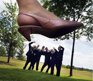 bride stepping on groomsmen picture